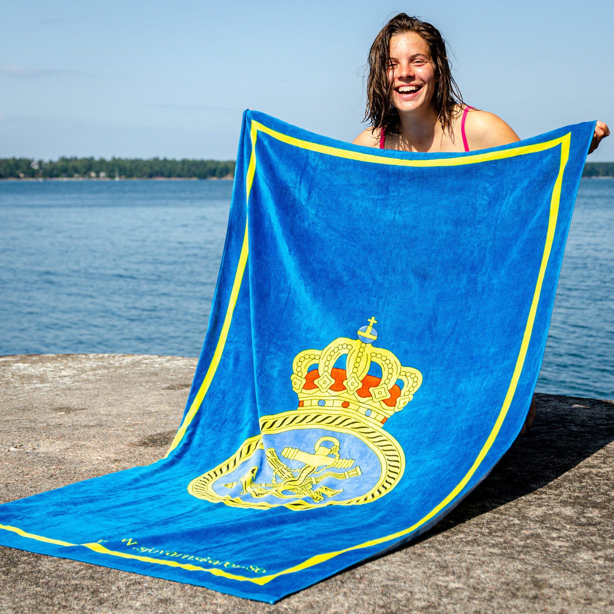 Stort härligt badlakan 100 x 180 cm med Sjövärnskårens emblem och texten www.sjovarnskaren.se i nedre högra hörnet.