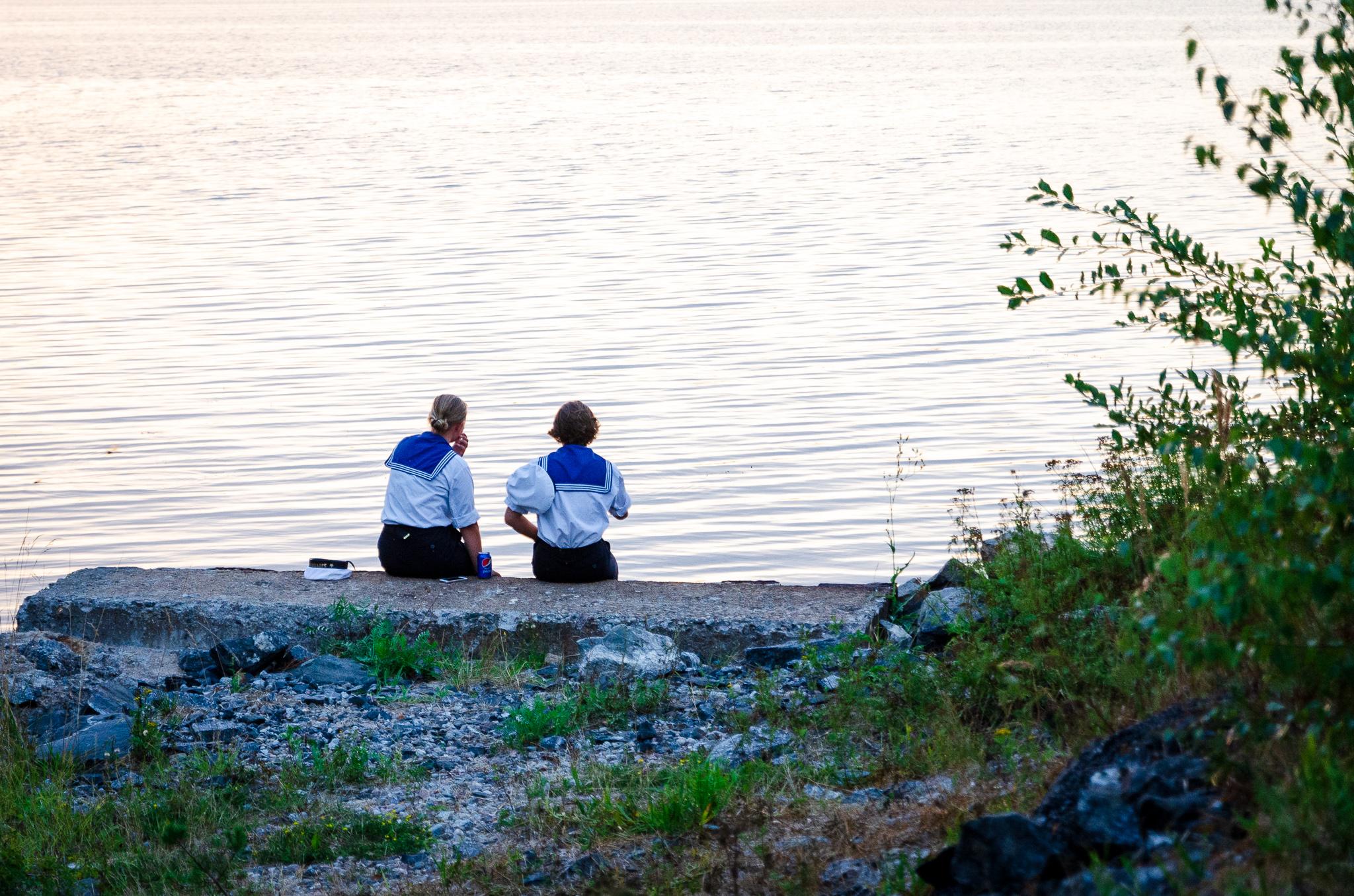 Sjövärnselever vid vattenbryn i solnedgång